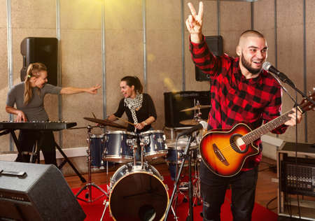Bearded guy soloist playing guitar in studio Stock Photo