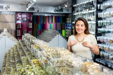 Young positive woman choosing necklace in shop Foto de archivo