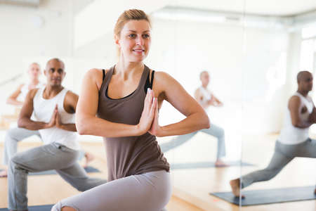 Young adult woman practicing yoga with group