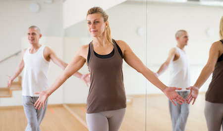 Young woman enjoying active dance with group in choreographic studio