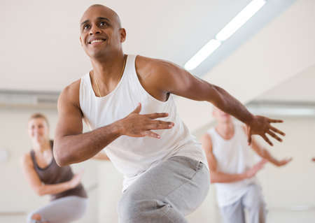 Hispanic man with group enjoying active dance in studio