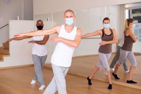 Man in protective mask practicing vigorous dance with group