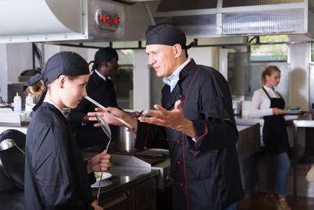 Exasperated chef scolding female employee Stock fotó