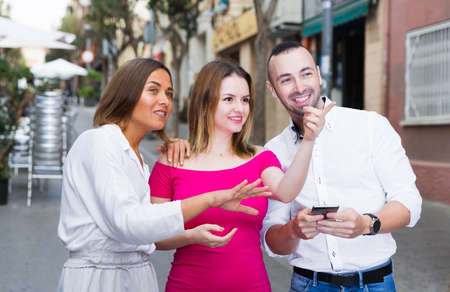 Stranger man is asking about way from young females who are walking