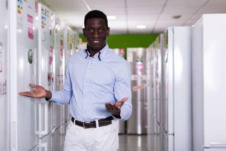Male standing near fridges in store of kitchen appliances