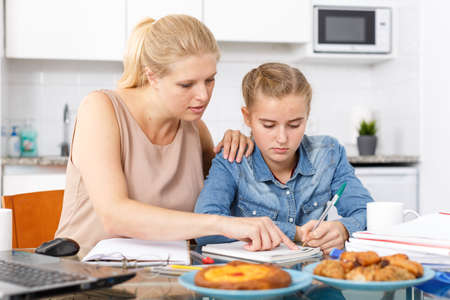 Woman helping daughter to do homework