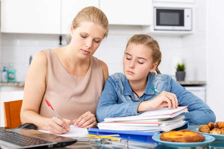 Mother helping daughter with home task