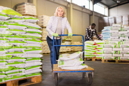 Portrait of middle aged woman working in warehouse, pushing handtruck with bags
