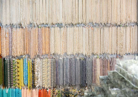 Various beads and necklaces of pearls on the showcase of jewelry store