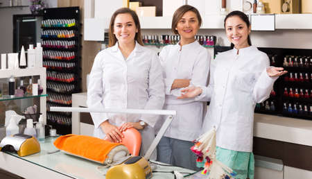 Smiling young team of nail technicians welcoming to modern beauty salon