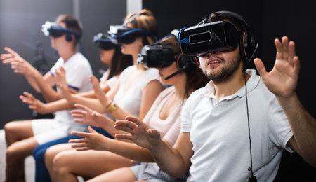 Guy with friends wearing VR headset Фото со стока