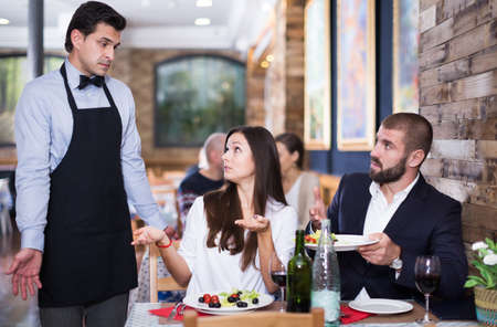 Adult couple expressing dissatisfaction with waiter about food
