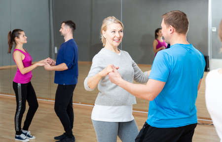 Mature dancing couple during group class