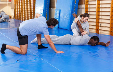 People fighting with coach at gym