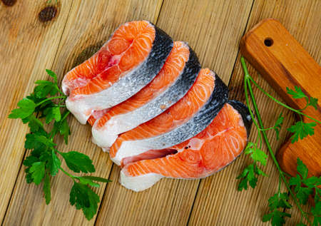 Fresh salmon steaks with lemon and greens