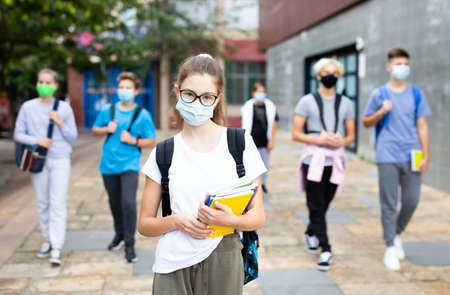 Teen girl student in face mask going to college