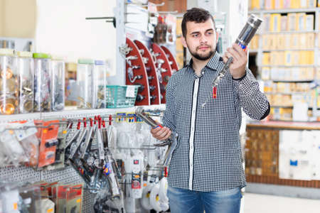 Young man customers choosing on best glue gun