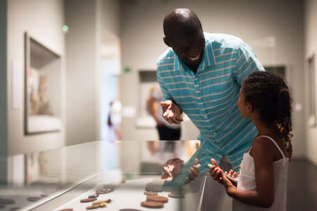Man and his daughter looking at showcase with exhibits