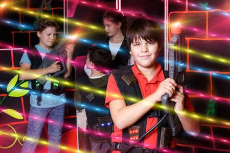 Portrait of positive boy standing with laser gun