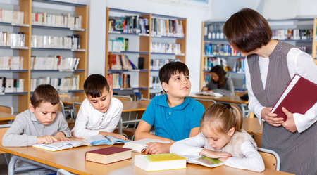 Group of school kids studying in school library with friendly female teacher
