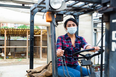 Masked hispanic woman sits behind the wheel of a tractor autocar during a pandemic. Stock Photo