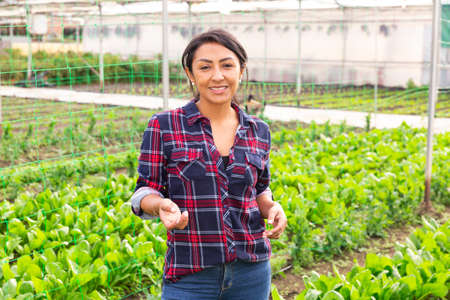 Portrait of smiling hispanic woman farmer, which is engaged in the cultivation of spinach.