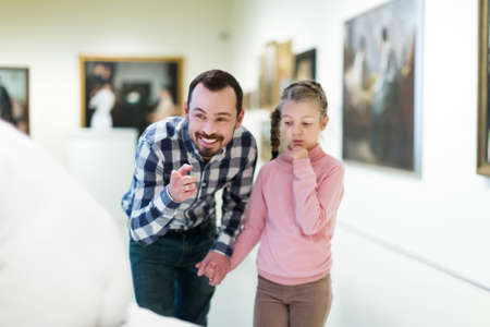 Father and daughter looking at classical statues