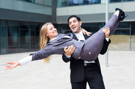 Businessman is carry his partner woman on hands because they are signed successful contract