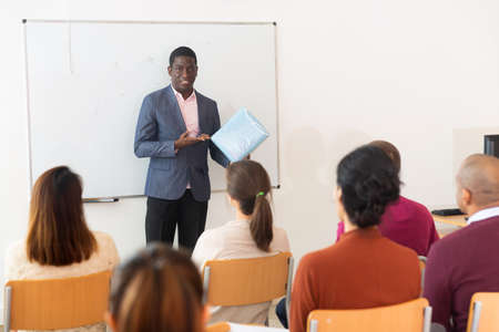 African american coach businessman giving talk at modern office conference to multiethnic team Standard-Bild