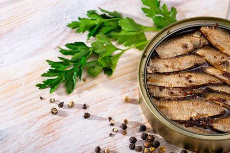 Tinned small smoked sardines on background with greens Standard-Bild