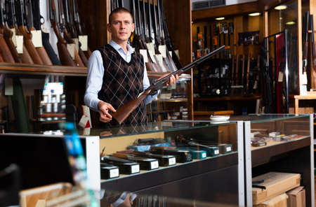 Gunshop seller with a rare collectible hunting rifle in hands