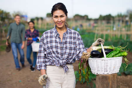 Portrait of female farmer with basket of vegetables on field
