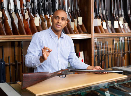 Handsome positive adult male in hunting shop with rare rifle in hands