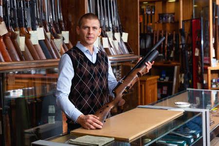 Gun shop salesman showing sporting air pump action rifle