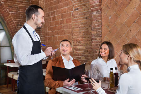 Male waiter taking order from visitors