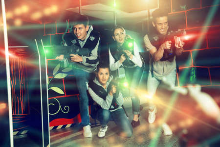 Modern young people with laser pistols playing laser tag on dark