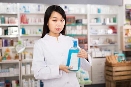 Chinese female pharmacist standing in pharmacy