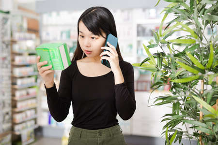 Chinese girl talking on the phone and choosing drugs at the pharmacy