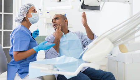 Woman dentist shows patient an x-ray Reklamní fotografie