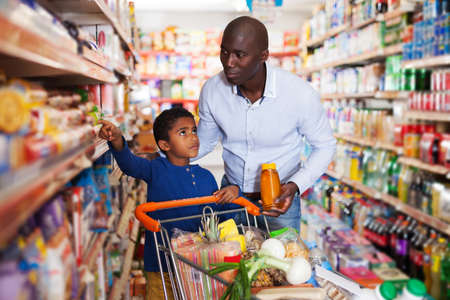 African American man with his son making purchases
