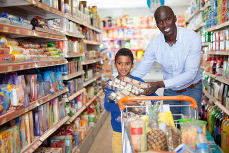 Portrait of happy friendly African family of father and tween son shopping in supermarket Foto de archivo
