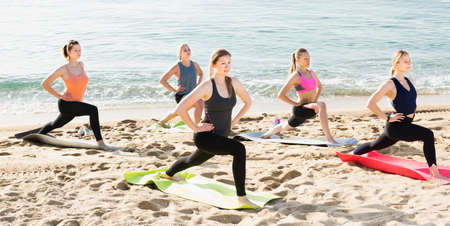 Yoga on sea beach, group of females training asana Standard-Bild