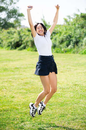 Happy young brazilian brunette girl in dress jumping at the garden
