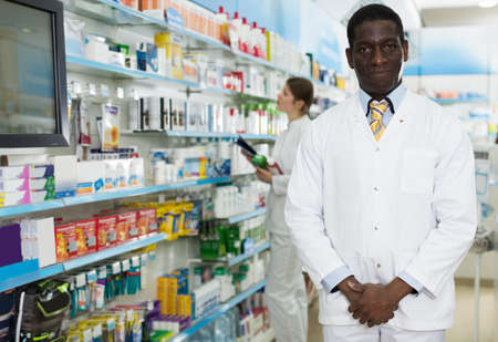 apothecary standing next to the shelves with medicines Foto de archivo