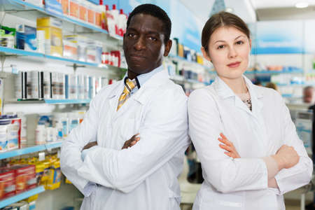 Two confident pharmacists standing on background with shelves of medicines in pharmacy
