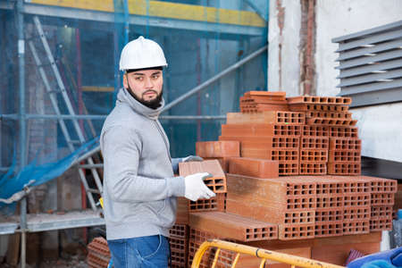 Bricklayer taking red bricks from stack