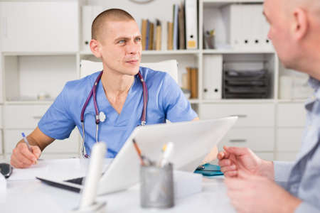 Doctor therapist shows to patient results of his tests Banco de Imagens