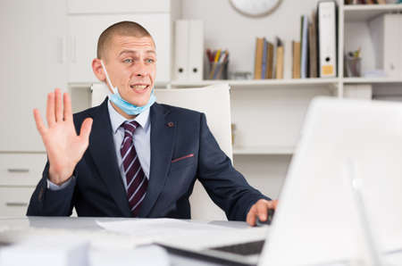 Head of the company in a protective mask leads online negotiations with business partners on a laptop