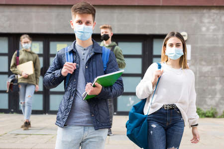 Teenagers in masks walking after lessons Banque d'images