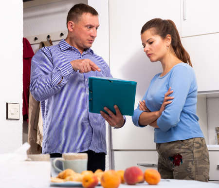 Frustrated woman talking to debt collector visiting her at home and demanding to pay debts
